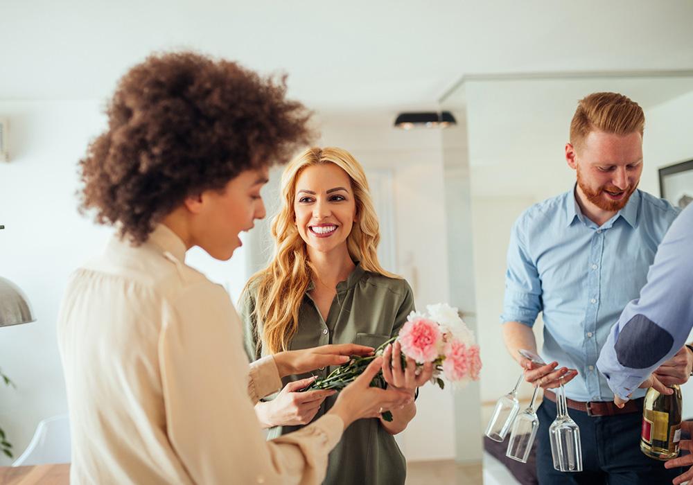Casal levando flores e vinho ao visitar casal de amigos