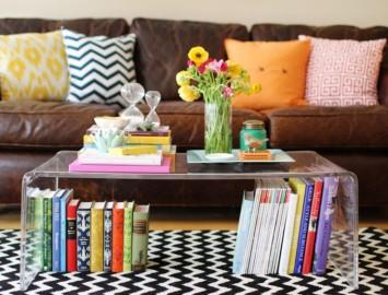 mesa de centro de acrílico decorada com livros flores e objetos decorativos pessoais