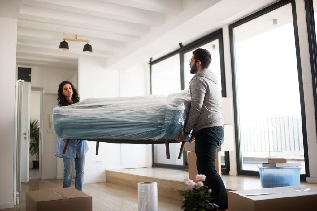 casal segurando um sofá na sala