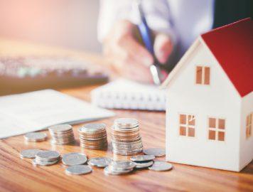 casa com moedas e anotações para controle de finanças