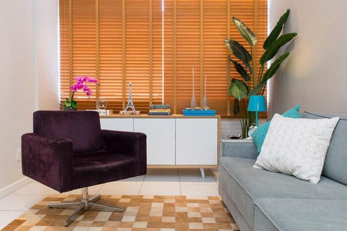 poltrona roxa em sala com sofá pequeno