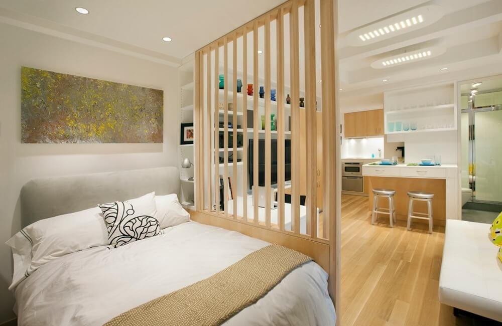 imagem de um apartamento studio, o quarto é dividido da cozinha e sala por uma madeira ripada