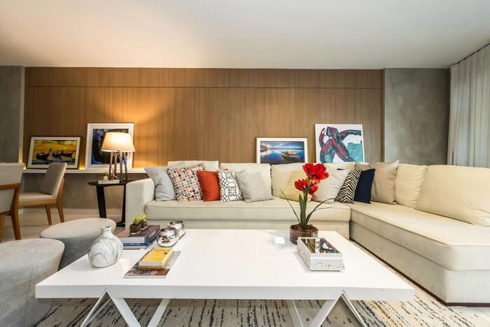 imagem de uma sala moderna e clara, com um sofá de canto com várias almofadas
