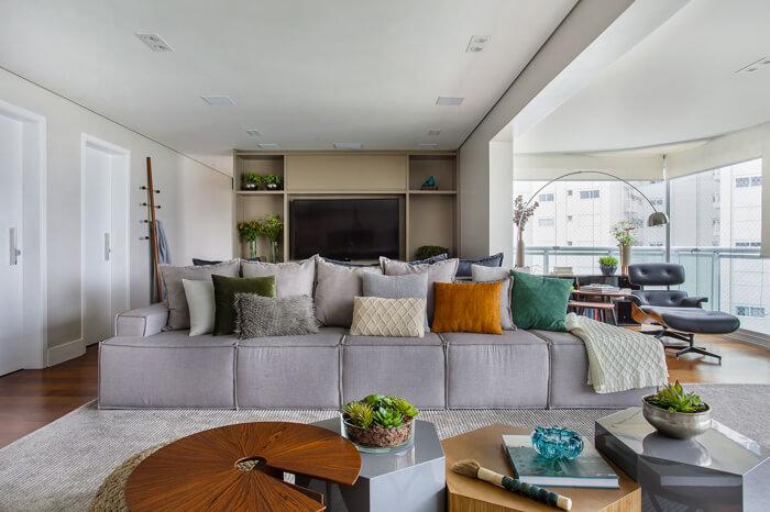 imagem de uma sofá cinza grande com bastante almofadas