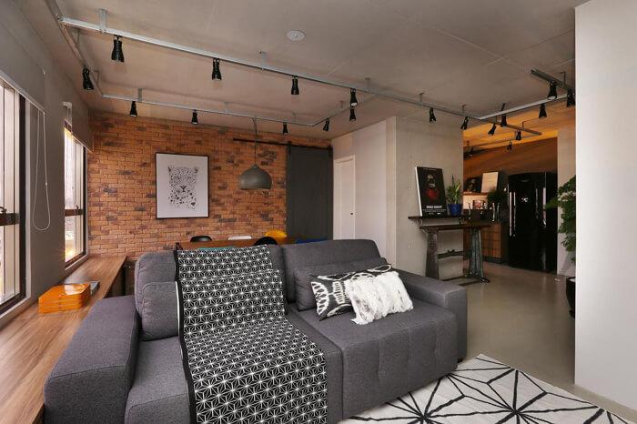 imagem de uma sala moderna e compacta com sofá cinza escuro