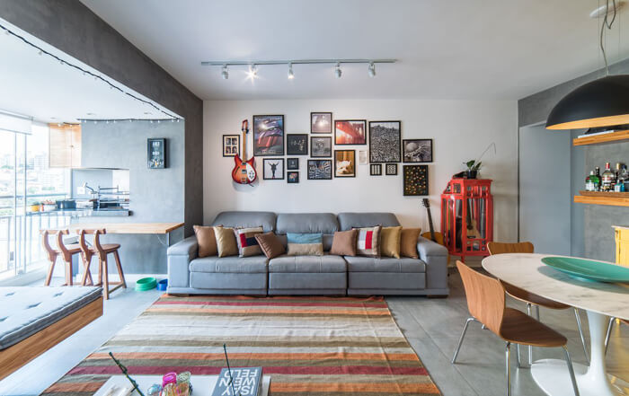 imagem de uma sala integrada com a churrasqueira e um sofa grande