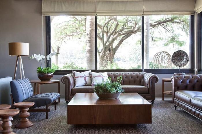 imagem de uma sala classica, com sofa marrom de couro