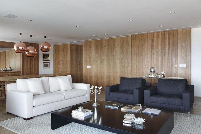 imagem de uma sala grande, com um sofá branco e duas poltronas azuis