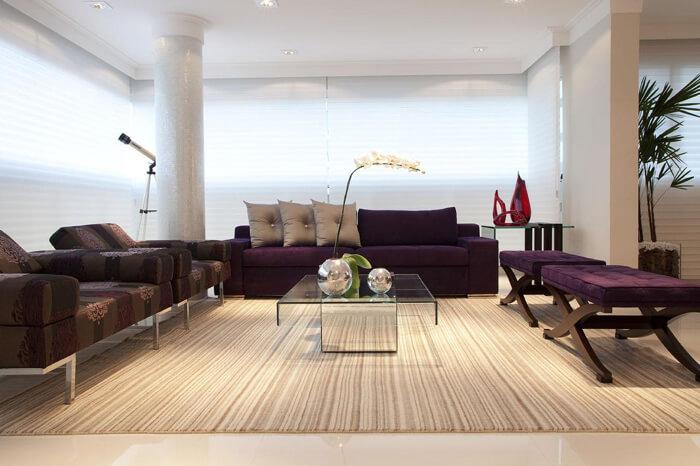 imagem de uma sala moderna com sofá e bancos roxos.