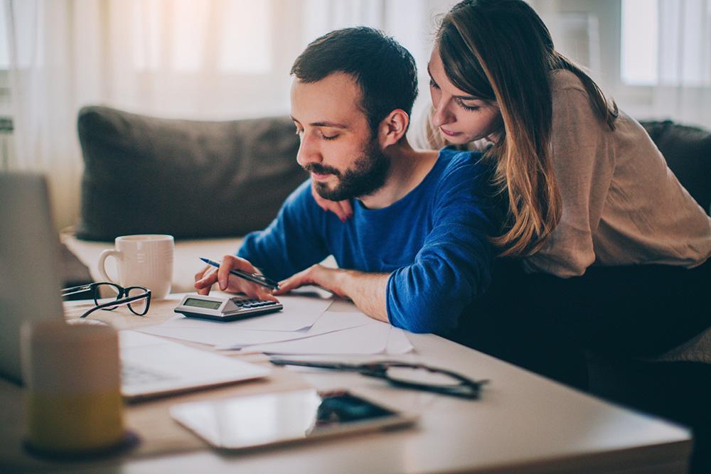 casal calculando custos para comprar ou alugar um imóvel