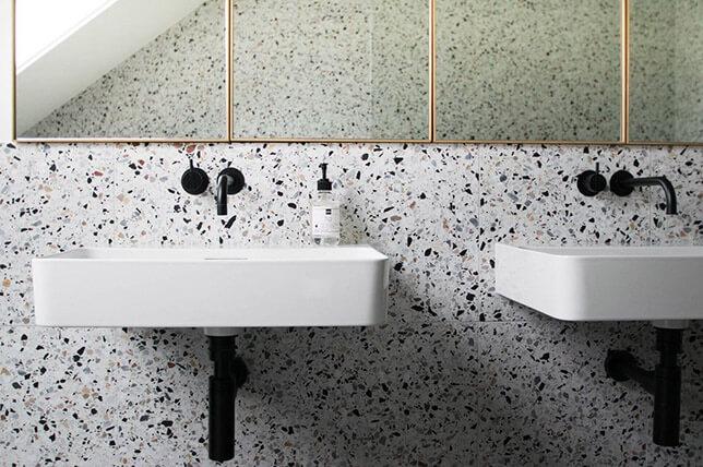 banheiro com pia suspensa e torneiras pretas de parede