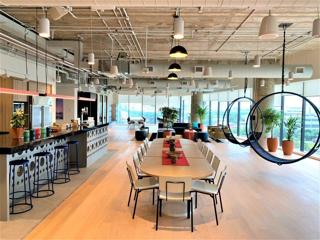espaço colaborativo com mesa, bancada e sofás