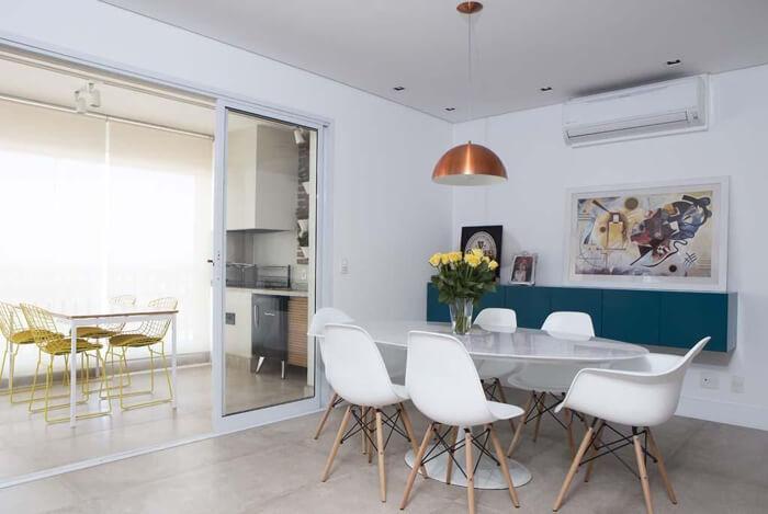 imagem de uma mesa de jantar em estilo tulipa e cadeiras brancas com os pés em madeira