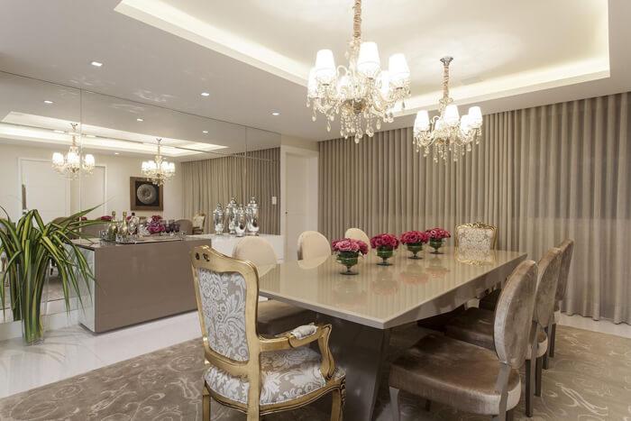 imagem de uma sala de jantar luxuosa, mesa de vidro e cadeiras em estilo poltrona
