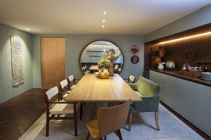 imagem de uma mesa de jantar amadeirada, cadeiras brancas e um sofá verde