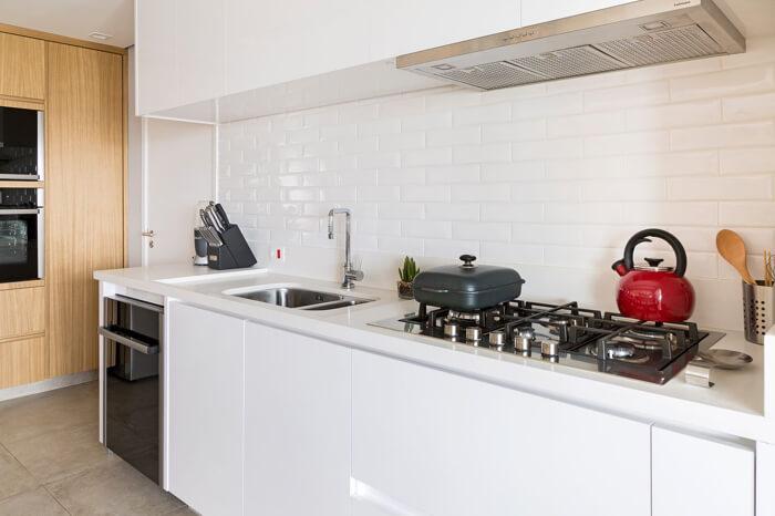 """imagem de uma cozinha branca com a parede de fundo em tijolos à vista brancos, conhecidos também como """"metrô white"""""""