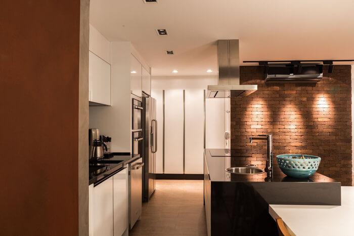 imagem de uma cozinha moderna com ilha e uma parede de tijolos a vista ao lado, com iluminação direcionadae