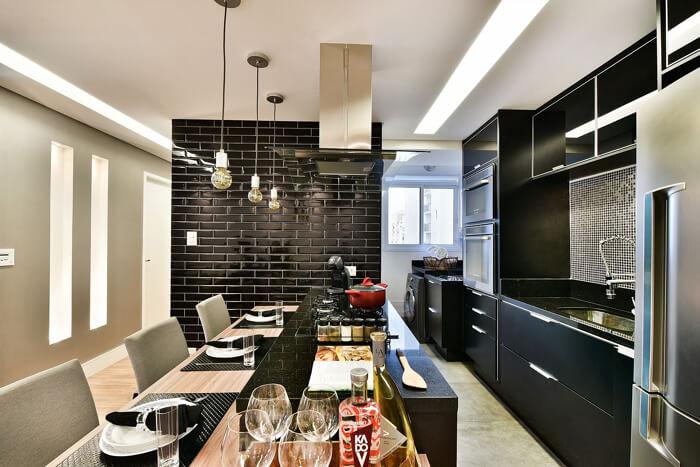 cozinha preta moderna, com uma parede de tijolo à vista pintada de preto
