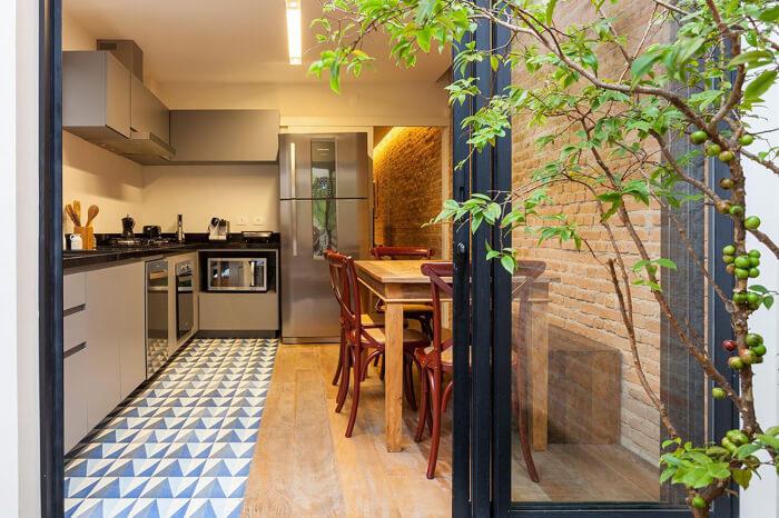 imagem de uma cozinha cinza moderna com uma parede de tijolo à vista