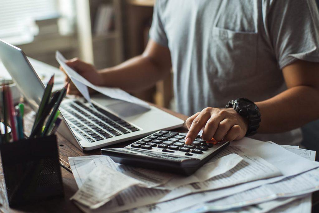Homem fazendo contas com calculadora, papéis e notebook