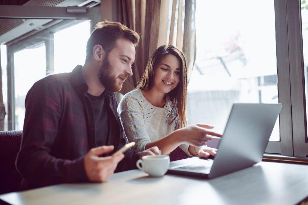 Homem e mulher sentados em frente a um notebook conversando