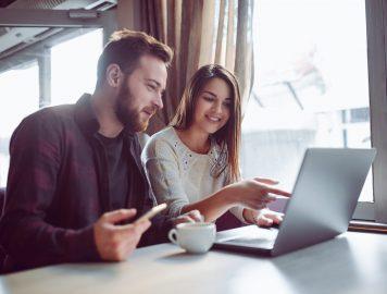 homem e mulher conversando e usando o notebook