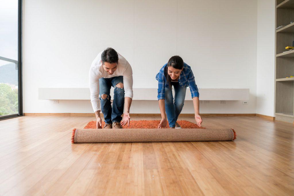 imagem de um casal abrindo um tapete em um apartamento antigo