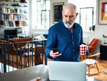 homem tomando cafe e usando o celular e computador