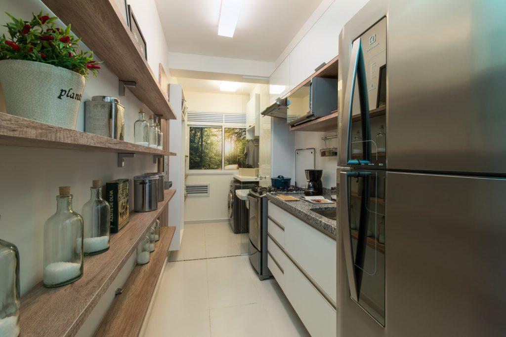 imagem de uma cozinha pequena, porém bem dividida, com prateleiras que armazenam potes e decorações