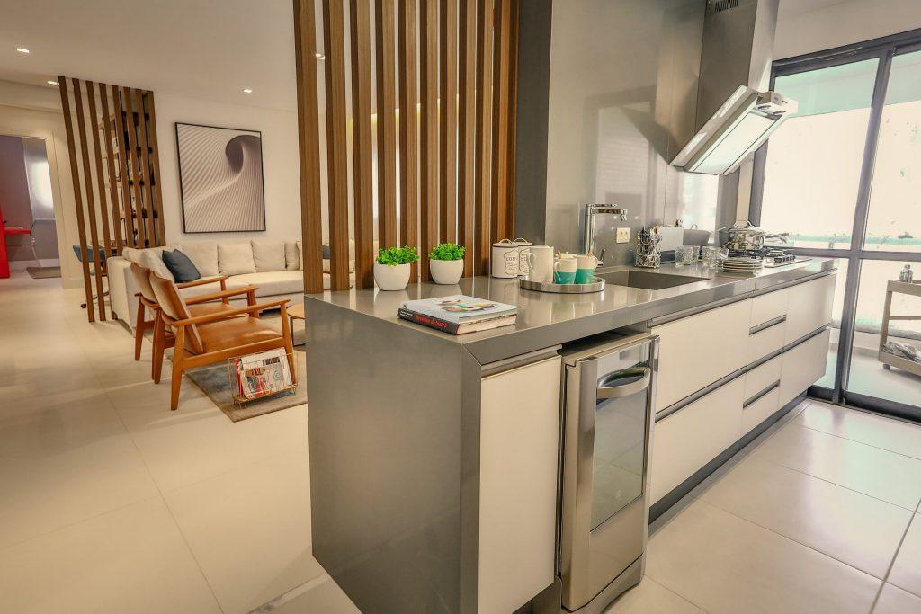 imagem de uma cozinha planejada, o ambiente está separado da sala por uma parede de madeira ripada