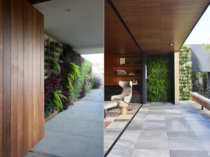 áreas externas revestidas em madeira e parede de plantas