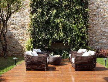 imagem de um ambiente externo com poltronas e uma parede verde