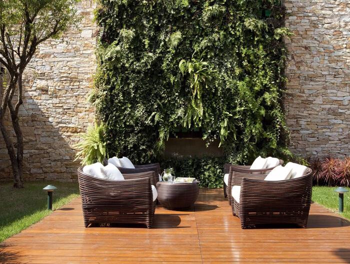 área externa com poltronas e parede com samambaias