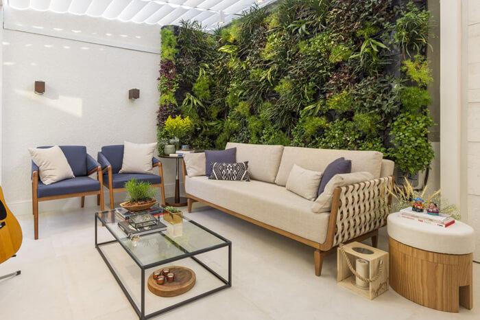 living com sofá, poltronas, mesa de centro e parede com plantas horizontais.