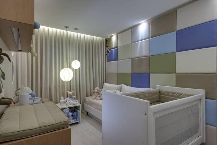 quarto de bebê azul com pendente circular com luz branca em frente à cortina