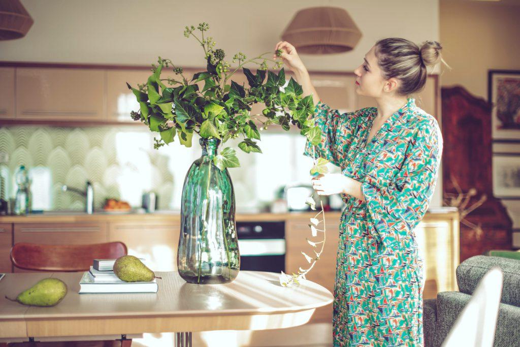 mulher arrumando vaso de plantas