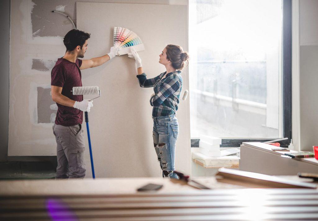 imagem com um casal escolhendo a tinta para pintar a parede