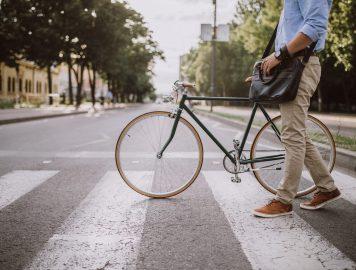imagem de um homem atravessando uma faixa de pedestre de bicicleta