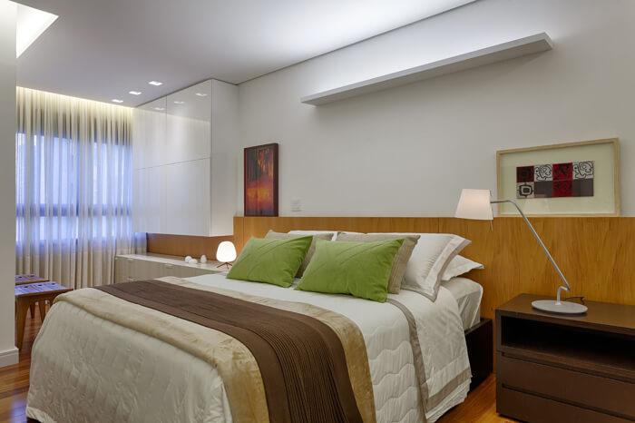 Cama box, com roupa de cama clara, travesseiros verdes e cabeceira de madeira.