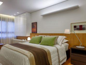 cama box com cabeceira de madeira e travesseiros verdes