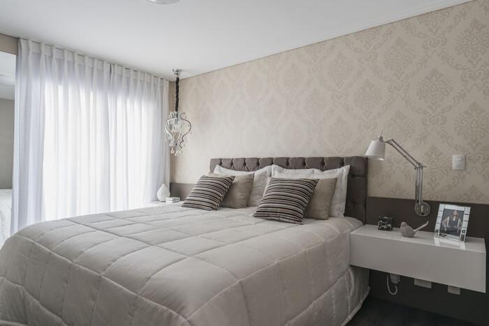 Cama box com roupa de cama clara e cabeceira cinza.