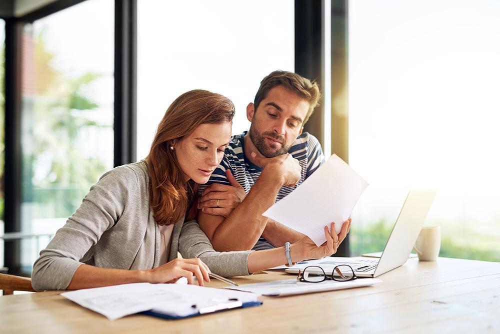 Um homem e uma mulher analisando papéis em frente ao computador