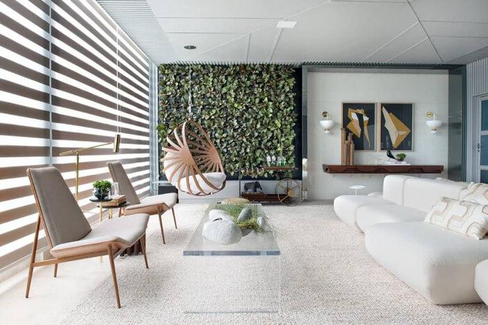 imagem de uma sala de estar com sofá, poltrona e uma parede verde de plantas