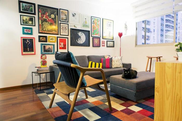 imagem de uma sala de estar com sofa, poltrona e quadros divertidos na parede