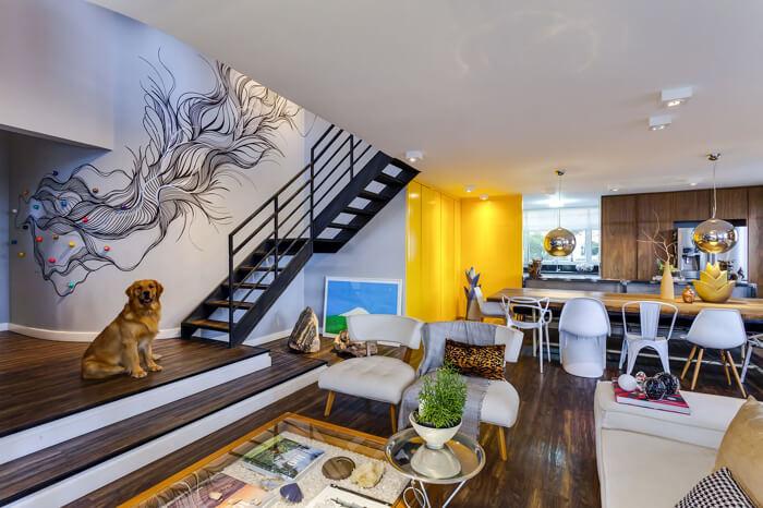 imagem de um ambiente  de sala e cozinha integrados, a parede da escada está desenhada com uma arte