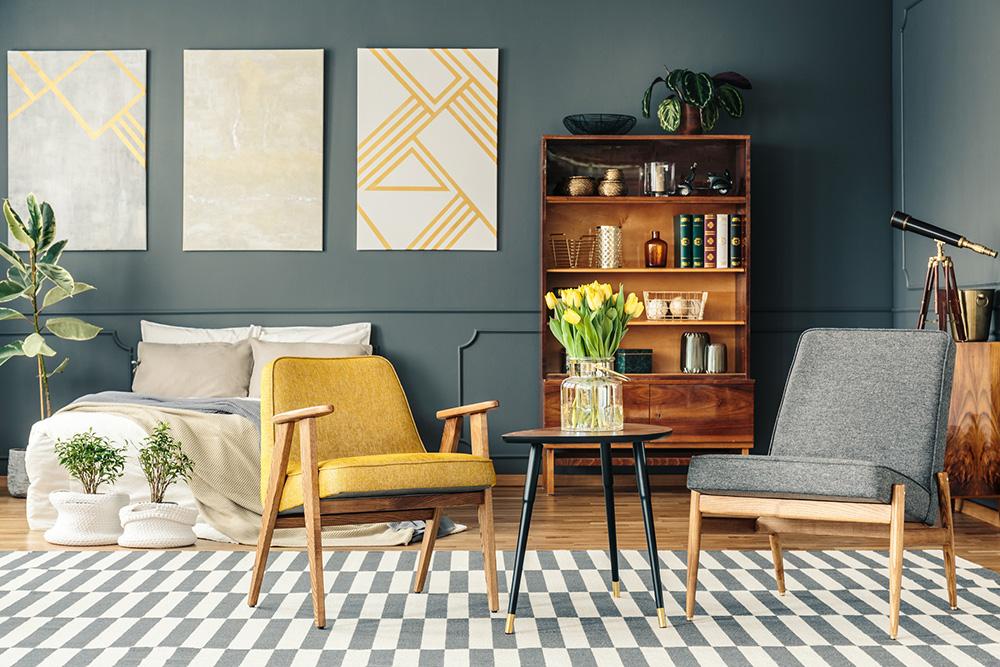 Sala com poltrona amarela e quadros na parede.