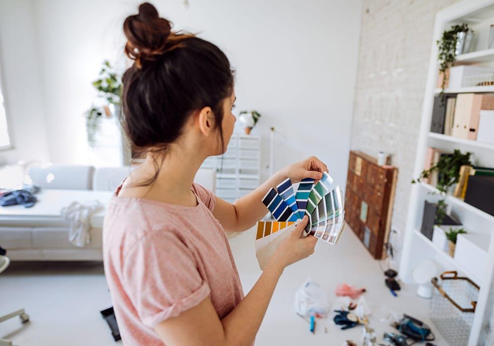 Moça escolhendo a cor para pintar o seu ap