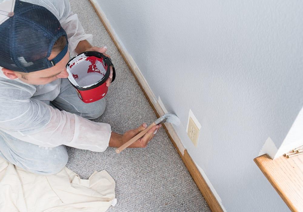 Pintor profissional pintando uma parede