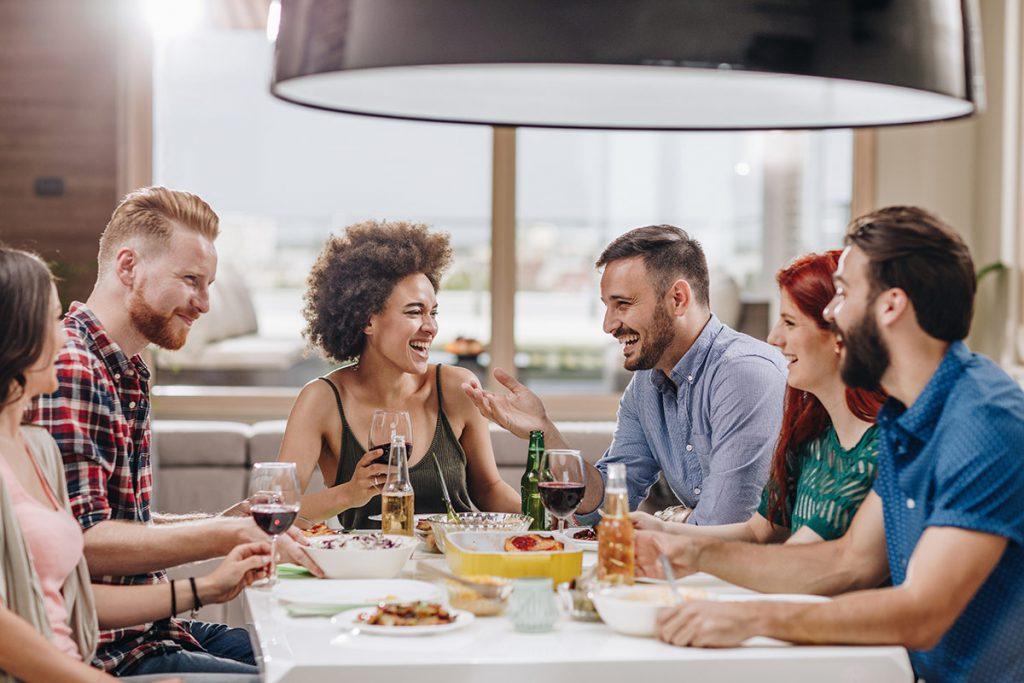 Amigos sentados ao redor da mesa comendo e bebendo