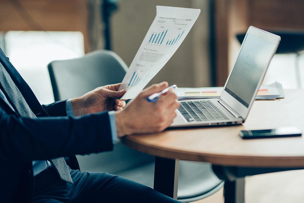Imagem de uma pessoa com uma folha na mão com gráficos e um notebook sobre a mesa